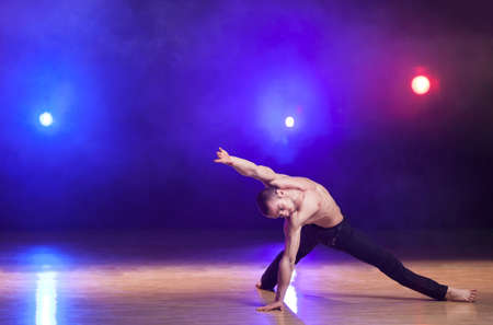 Young and muscular man performing a contemporary dance pose on a stage. photo