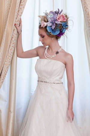 Gorgeous woman in bride dress having a large bun with artificial flowers  photo