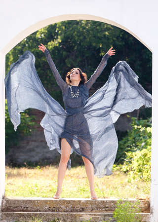 transparent dress:  Elegant woman, in long transparent dress, posing in a carefree attitude with the folds of her transparent dress, up in the wind