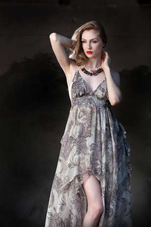 Alluring red-haired woman in long folded grey dress, with a sensitive, but strong attitude  photo