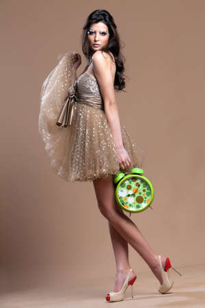 Beautiful woman in elegant dress holding a big green old fashion clock in her hands. Stock Photo - 30529380