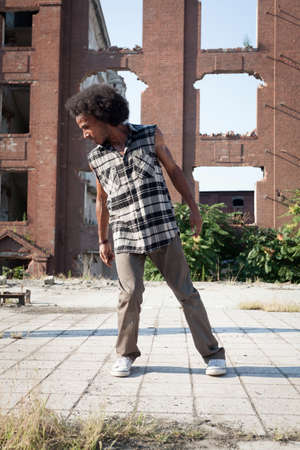 hip hop dancing: Young African American man hip hop dancing in an urban square, lit by a bright sun over high-rise buildings