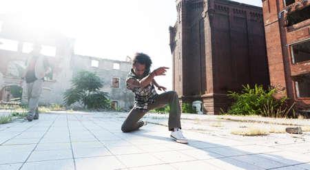 baile hip hop: Hombre joven del afroamericano que termina fuera de su rutina de baile de hip hop con una reverencia de rodillas con gracia en la pavimentaci�n de una plaza urbana con retroiluminaci�n por el sol.