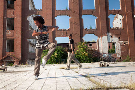 hip hop dancing: Young African American man hip hop dancing in an urban square with a friend backlit by a bright sun over high-rise buildings Stock Photo