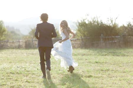 boda: Pareja casada corriendo en un campo, la diversión y la sonrisa. Ella está mirando hacia atrás. Foto de archivo