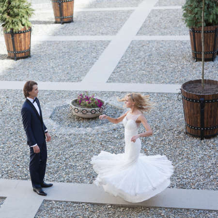 pirouette: Beautiful bride making a pirouette for her groom, while he looks at her charmed by her beauty. Stock Photo