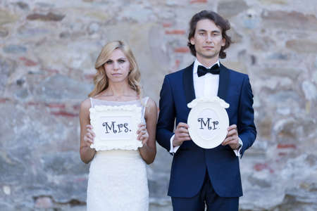 mr and mrs: Newlywed couple acting funny, with white cartons of Mrs. and Mr.?, posing front like offenders.
