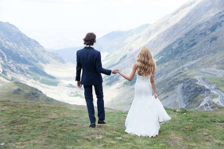 admires: Married couple admires the beautiful view of the mountains, holding hands.
