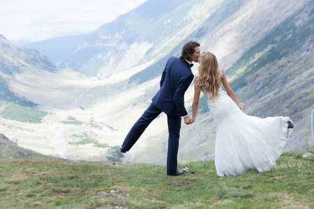 mountains and sky: Married couple kissing in the nature, acting like they are dancing. Stock Photo