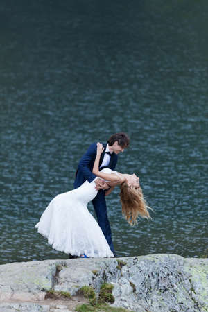 newlywed couple: Married couple kissing nears a lake, acting romantic and joyful. Stock Photo