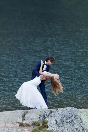 matrimonio feliz: Pareja bes�ndose Casado se acerca a un lago, actuando rom�ntica y alegre.