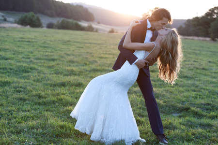 women kissing: Married couple kissing on a grass field. Stock Photo