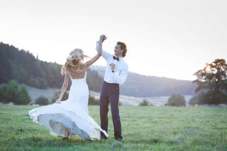 the happy bride: Married couple dancing in the middle of a field, showing joy, love and happiness.