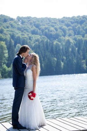trash the dress: Beautiful married couple kissing near a lake, standing on a foot bridge.