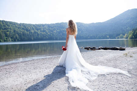 Beautiful bride trashing her white long dress and retinue at the lake beach, watching the view.