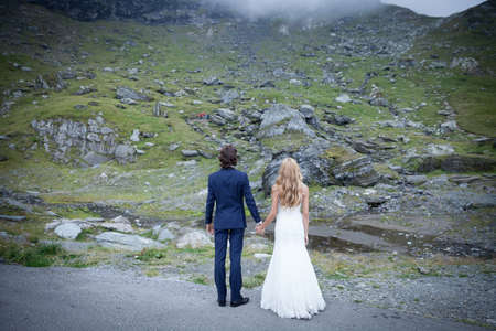 trash the dress: Married couple holding hands, staring at some mountain rocks. Conceptual image refering to a new beginning, with many challenges in life. Stock Photo