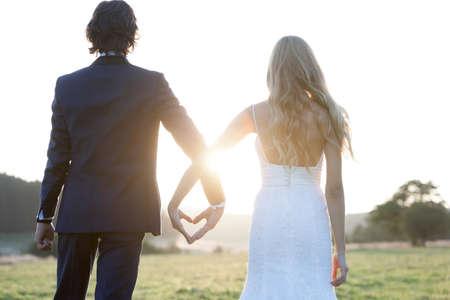 casados: Pareja casada ver el atardecer, formando un coraz�n con sus manos.