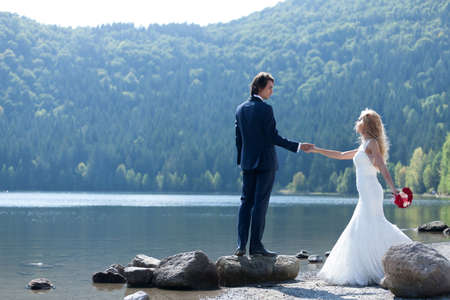 trash the dress: Beautiful married couple acting very romantic near a lake. The groom stands on a big rock and invites his bride close to him so she can see the view.