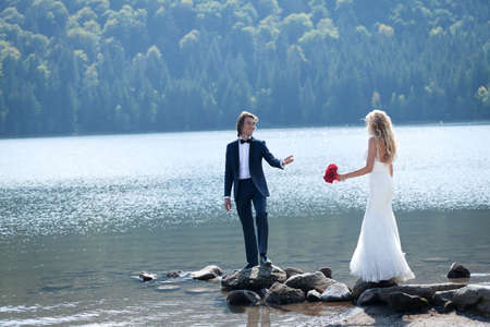 Married couple having a relaxing and fun moment at the lake. The groom dares his bride to follow his steps on some rocks.