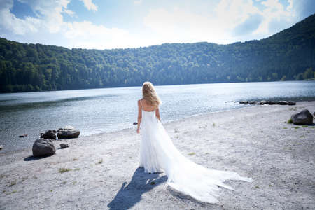 trash the dress: Beautiful bride trashing her white long dress and retinue at the lake beach, watching the view.