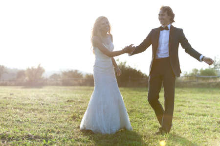 trash the dress: Beautiful married couple having fun and smiling on a field. Stock Photo