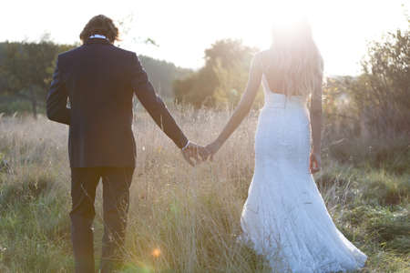 back to back couple: Beautiful married couple taking a walk on a field, watching the sunset. Stock Photo