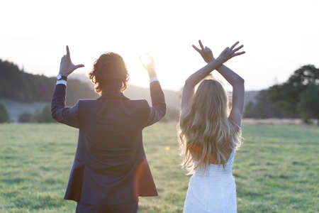 bride: Married couple standing at the sunset, forming by fingers the word LOVE.
