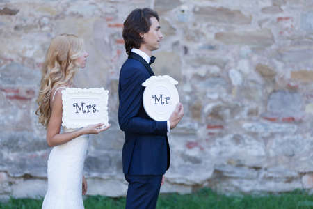 "mr and mrs: Newlywed couple acting funny, with white cartons of ""Mrs. and Mr."", posing profile like offenders."