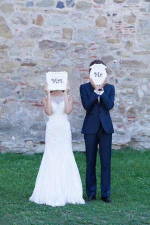 trash the dress: Newlywed couple acting funny, with white cartons of �Mrs. and Mr.� covering their faces with them. They are expressing a crazy, interactive and funny couple. Stock Photo