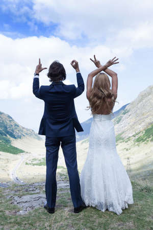 trash the dress: Married couple staring at the beautiful view, at mountains, forming by fingers the word �LOVE�.