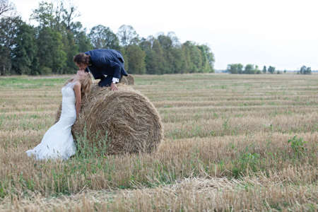 be kissed: Beautiful married couple acting very romantic on a field of bales. He climbs the bale to kiss her lips while she lays her head to be kissed.