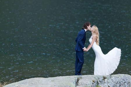 trash the dress: Married couple kissing nears a lake, acting romantic and joyful. Stock Photo