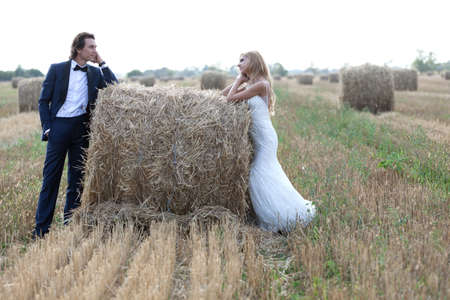 trash the dress: Married couple staring one another deeply in love, on a hay bale. Stock Photo