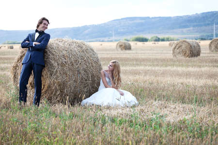 trash the dress: Married couple having fun on a field with hay bales. Stock Photo