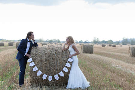 """recien casados: Pareja casada de pie con los codos apoyados en un fardo de heno que se escriben """"recién casados""""."""