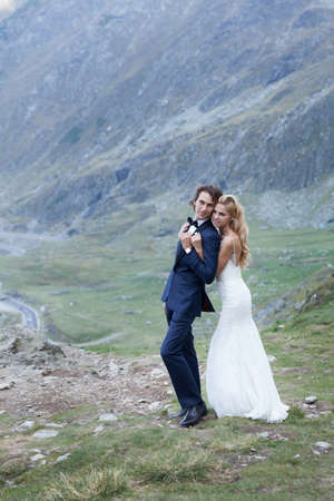 trash the dress: Married couple admiring the beautiful view of mountains. She holds him gentle and protective from the back and smiles.