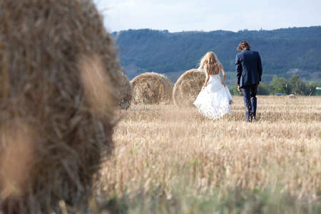 trash the dress: Married couple relaxing on a field with hay bales, feeling free and in love.