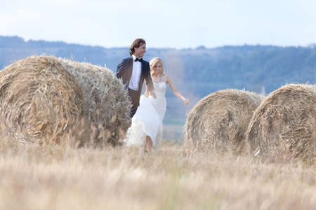 trash the dress: Young married couple playing like kids, running between hay bales. Stock Photo