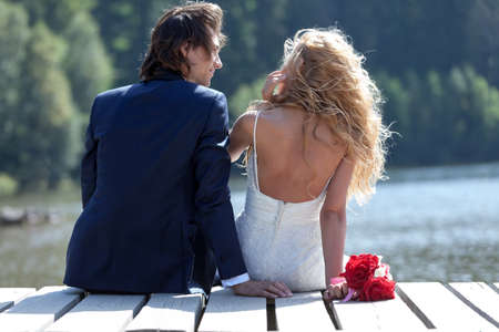 admires: Bride and groom standing on a footbridge at the lake. He admires her beauty while she's playing with her hair.