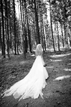 trash the dress: Beautiful bride trashing her long dress and retinue in the woods. Black and white image with grain added as effect.