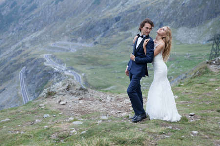 trash the dress: Married couple enjoying the beautiful view. He admire how the breeze caressing her face. Stock Photo