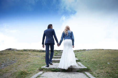 trash the dress: Married couple taking a walk on a stepped path. It looks like they are climbing stairs to the sky. He gives her a confident look.
