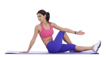 cross leg: Sitting on the floor, cross one leg or ankle over the other thigh. Gently press on the thigh as you rotate your body toward the stretching leg. Stock Photo
