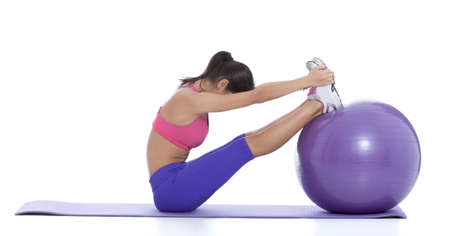Put your heels on the ball, slowly bend forward, allowing your arms to hang down in front of you.