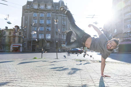 street dance: Young man doing street dance, feeling happy and energetic. Stock Photo