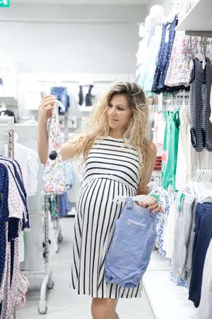 6addf128b  45413563 - Mujer embarazada encantadora joven en busca de un poco de ropa  de bebé en una tienda para su nuevo bebé.
