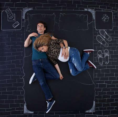 position d amour: Jeune couple dormir dans le lit dans des positions dr�les. Banque d'images