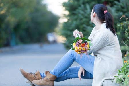 mujer alegre: mujer joven con un hermoso ramo de flores sentado en una carretera. Foto de archivo
