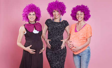 wigs: Young happy pregnant women with wigs touching their bellies.