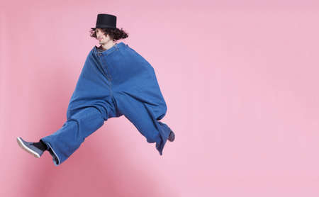 extra large: Young man wearing extra large pants and a top hat, jumping high. Stock Photo